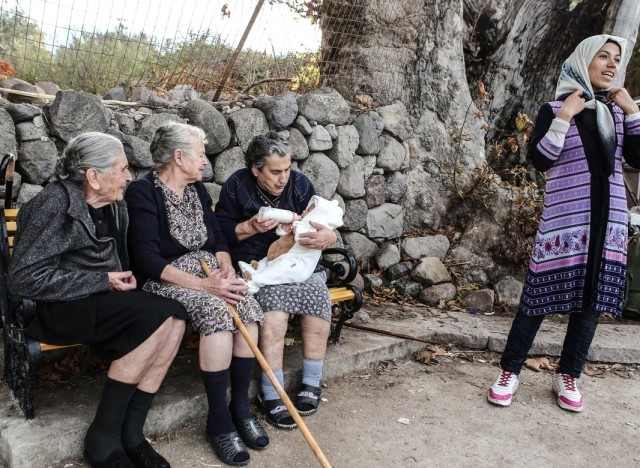 Three elderly women feed a migrant child at the island of Lesbos, Greece on October 17, 2015. / ????? ??????????? ???????? ??????? ??? ???? ???? ???????? ???? ?????, ???? 17 ????????? 2015.