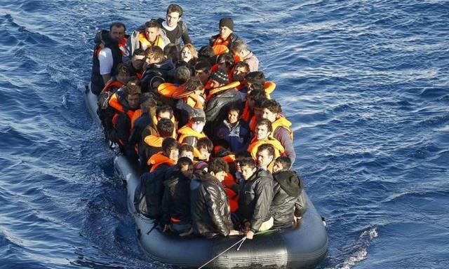 A dinghy of refugees and migrants is towed by a Turkish Coast Guard fast rigid-hulled inflatable boat on the Turkish territorial waters of the North Aegean Sea